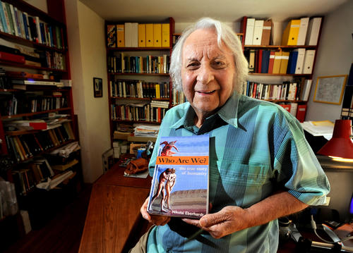 Author Nikolai Eberhardt holds his latest book Who Are We? The True Story of Humanity in his home office Wednesday.