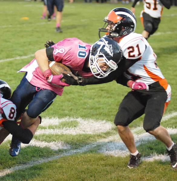 Petoskey running back Tony DeAgostino (10) struggles for extra yardage against Cheboygan's Hunter Filice Friday during a 33-14 Northmen win at Curtis Field.