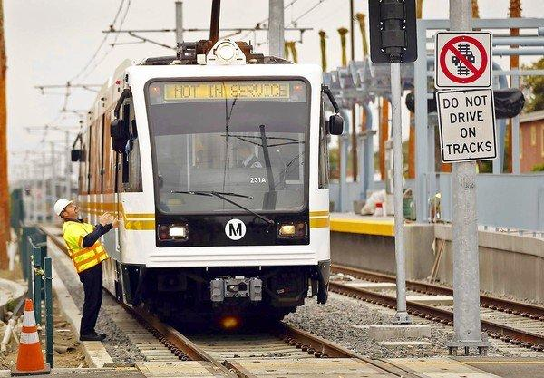 A worker checks a Metro Expo Line train before testing a street crossing last spring.