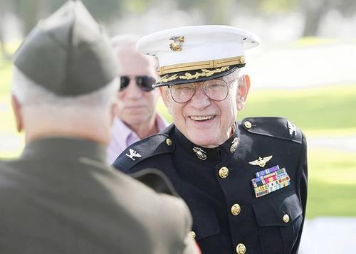Edison Miller, a Marine, happily greets a guest after being recognized during the POW/MIA Recognition Day ceremony hosted by Assemblyman Allan Mansoor at TeWinkle Park in Costa Mesa on Friday.