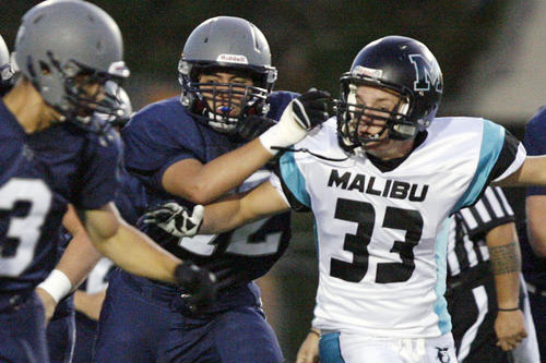 Flintridge Prep's Cameron Wen, center, blocks Malibu's Matt Vincent, right, during a game at Occidental College in Los Angeles on Friday, September 21, 2012.