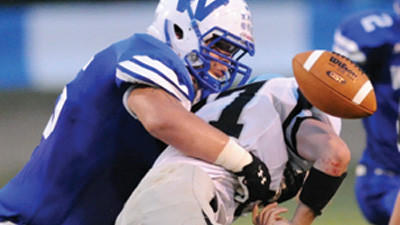 Windber's Shane Almodovar, left, forces Blacklick Valleys' Grant Reigel to fumble in high school football action in Windber Friday night. Blacklick recovered the fumble.