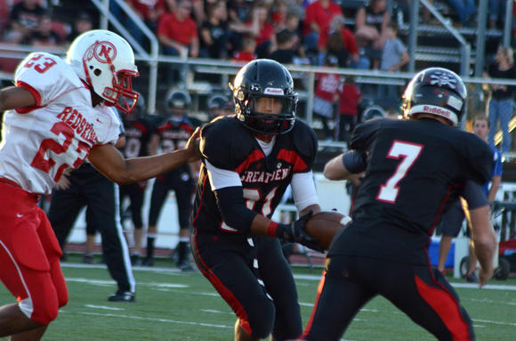 Great Bend's Johnny Allende (21) hands a reverse to quarterback Bryce Beck (7). The first play from scrimmage went 24 yards for a score. Wichita North's Davariss Simpson tries to break it up.