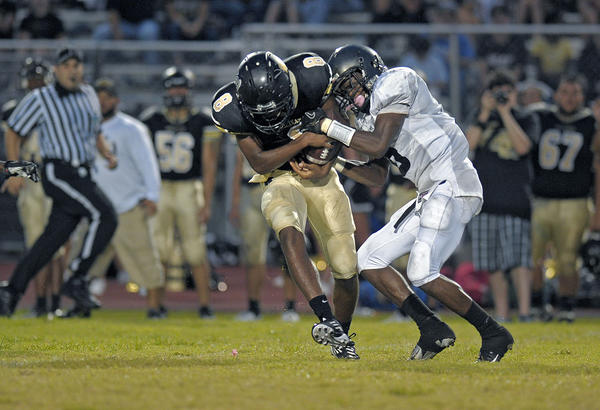 Western defensive back Morris McKeithen and Everglades receiver Andre Hallmon fight for the ball intended for Hallmon during the first half of their game.