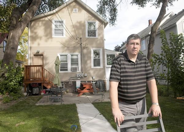 Forest Park landlord Mark Hosty stands in front of the house that he rehabbed. He applied for and received an adjustment on the property taxes, but getting his overpayment to Cook County returned proved to be a taxing experience.
