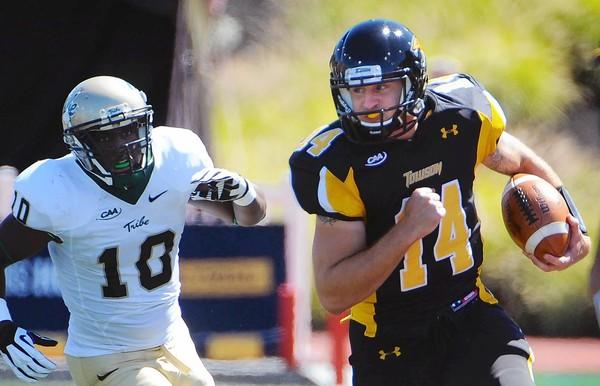 Towson quarterback Grant Enders, right, runs down the sideline pursued by William & Mary's Jabrel Mines in last week's game against William and Mary at Johnny Unitas Stadium. The Tigers are hosting St. Francis on Saturday at 7 p.m. in the university's homecoming game.