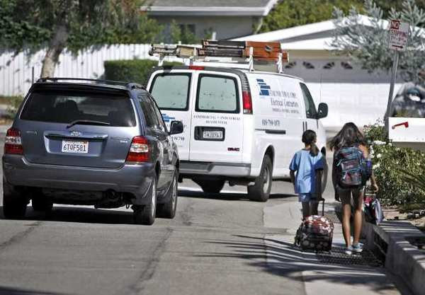 Cars take a wide right turn to avoid La Canada Elementary school students walking on Fairview Drive at Angeles Crest Highway on Thursday, Sept. 20, 2012.