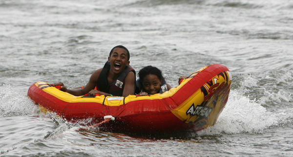 Myles Vaughn, 15, left, and Nicole Orr, 12, both of Lake Mary, enjoy tubing on the lake at Camp Wewa in Apopka, Fla. Saturday, September 22, 2012.  The YMCA of Central Florida, along with the Florida Blue and region¿s Jack and Jill group, is sponsoring a World Wide Day of Play event on Saturday Sept. 22 to focus on getting kids moving and fighting obesity at Camp Wewa in Apopka, Fla.