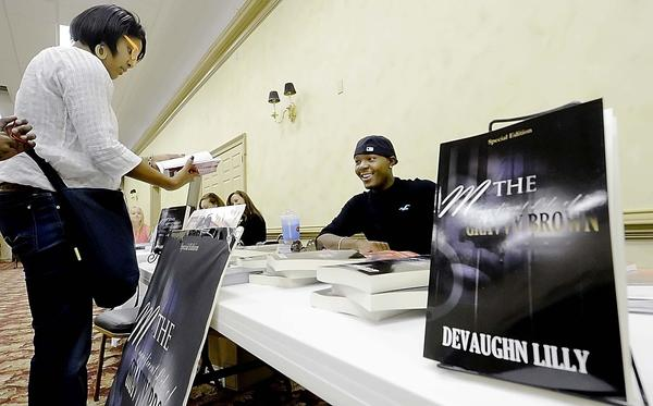 Seslie Daniels of Hagerstown looks over a book written by Devaughn Lilly of Cleveland, Ohio, at the Urban Book Festival held Saturday at Bridge of Life Center.