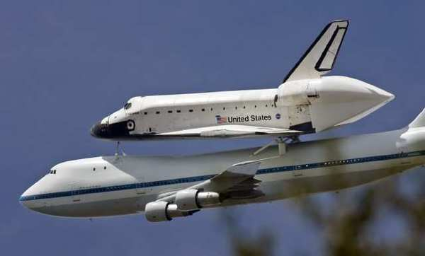 The space shuttle Endeavour on top of a transport 747 banks over the La Canada High School football field after a pass over JPL during it's trip to LAX on Friday, September 21, 2012.