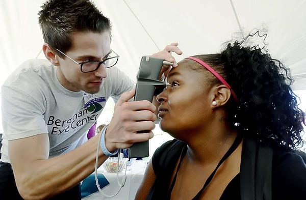 Mark Bergman of Bergman Eye Center checks for glaucoma on Shannon Venable at Convoy of Hope on Saturday.