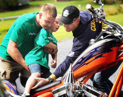 Joshua Scoble, 6, of Emmaus is hoisted by his father David Scoble, left, onto a motorcycle owned by Robert Manogue of Walnutport, right, at the fundraiser for Joshua at Indian Trail Park Saturday. Joshua has fibrodysplasia ossificans progressiva. A hundred bikers rode through the area during the afternoon to raise funds to help with Joshua's medical costs.