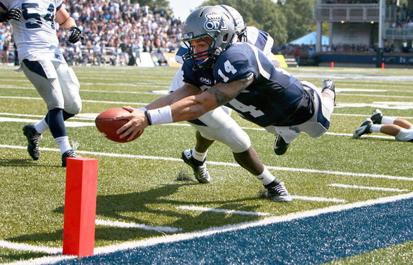 Old Dominion quarterback Taylor Heinicke dives into the endzone for a second quarter touchdown as Jay Colbert of New Hampshire tries to knock him out of bounds Saturday in Norfolk.