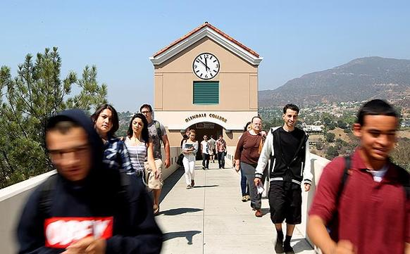 Students walk along a bridge towards a parking structure at Glendale Community College. Students at California's community colleges are having a tough time getting into classes they need to further their careers.
