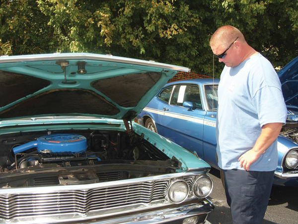 Tony Kinzer, 44, of Boonsboro, checks out the engine of the 1964 Ford Galaxie 500 that his late friend Mike Kline helped him pick out at the Mike Kline Memorial Car Show & Bike Bash on Saturday at Cancun Cantina West in Hagerstown.