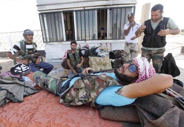 Free Syrian Army fighters rest at a Syrian-Turkish border crossing captured by the rebels last week.