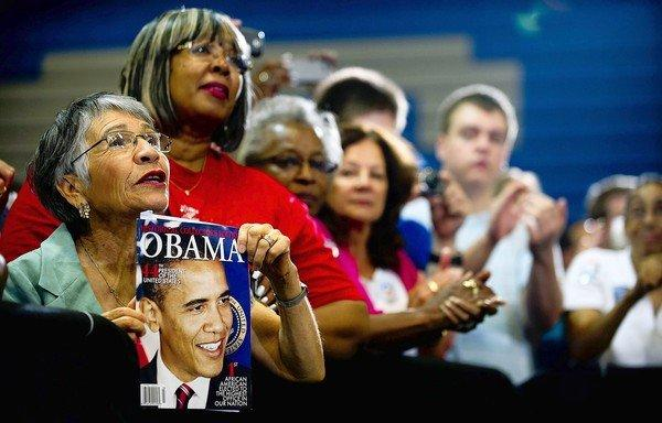 Maria Gray, left, holds up a magazine as President Obama speaks during a campaign event at Canyon Springs High School in Las Vegas.