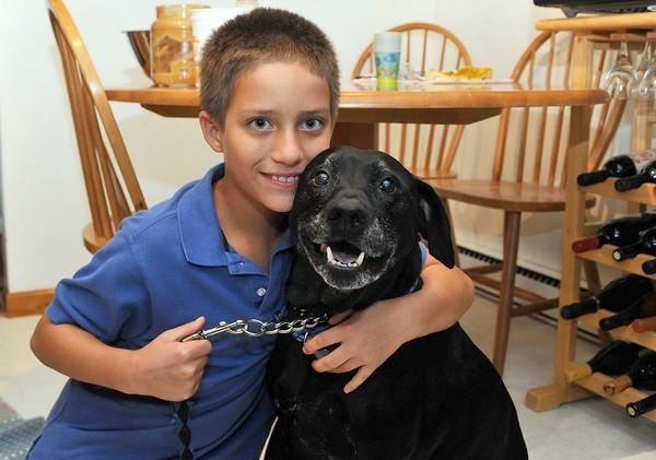 Zachary McGaughey, 9, of Bethlehem Township poses with Isaac, the family's dog. Zachary shows us how to make cheap treats for dogs.