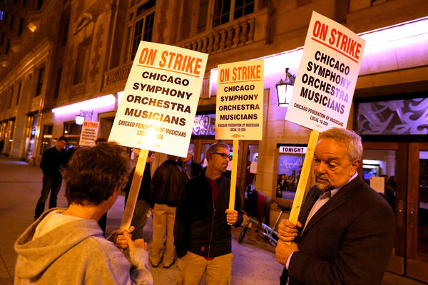 Striking musicians, left to right, violinist Nisi Howell, bassist Rob Kassinger, and President of Chicago Federation of Musicians Gary Matts, stand outside of Symphony Center in Chicago.