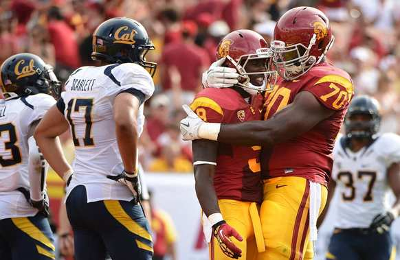 USC receiver Marqise Lee is congratulated by teamma Aundrey Walker after catching a touchdown pass aga