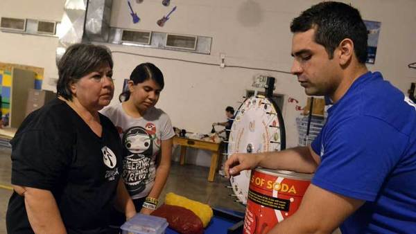 Rosalinda Luna (left) a Zumba participant for four years and her daughter Daisy Benavides, 15, (middle) speak with a public health department worker Jorge Torres about different types of healthy food and exercises at the Latino Health Awareness celebration that was held at the Brawley Boys and Girls Club on Saturday.
