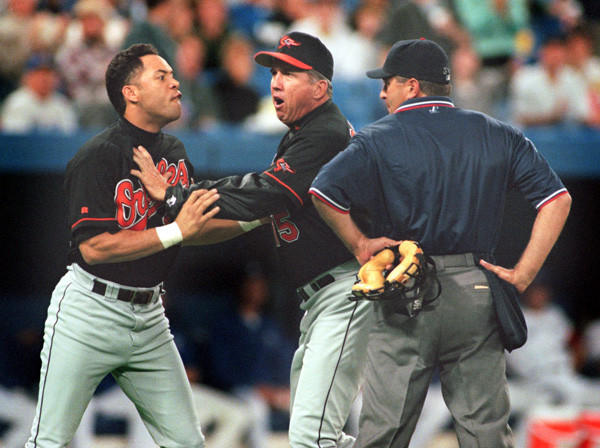 Roberto Alomar spit on umpire John Hirschbeck as Orioles manager Davey Johnson holds him back.