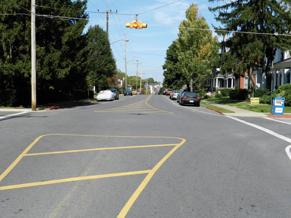 The yellow lines painted in the 500 block of Summit Avenue at the intersection with Reynolds Avenue split several feet apart, appearing to direct traffic to veer to the right several feet as they pass through the intersection. A flashing yellow light hangs above the intersection. Many motorists who drive along Summit Avenue, however, simply drive straight through and do not follow the lines.
