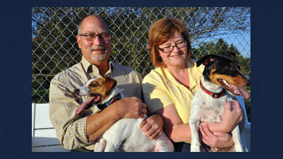 Jim Atchison and his wife Sharon sit with Jger (left) and Kobi (right) at Jger and Friends Dog Park.