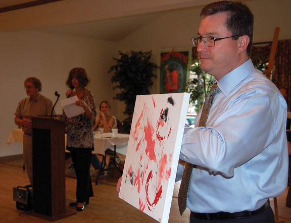 Gerald Turner of Chambersburg, Pa., displays an art print as it is auctioned Sunday to benefit the Franklin County (Pa.) 4-H Therapeutic Riding Center. The print was made by one of the center's horses with some human assistance.
