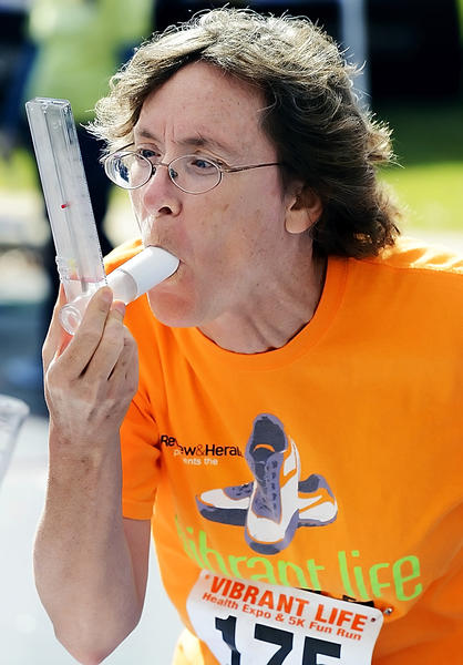 Laurie Wilson of Catonsville, Md., uses a Peak Flow Meter to check her expiratory flow at the Vibrant Life Health Expo and 5K Fun Run on Sunday