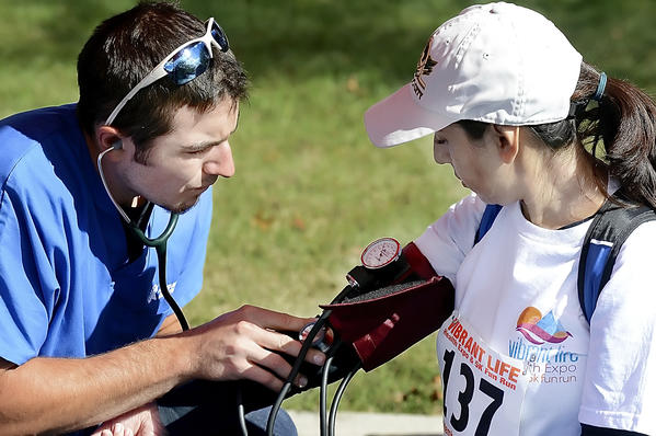 Benjamin Wilkinson, a first responder with the Needmore (Pa.) Volunteer Fire Co. checks the blood pressure of Alexandra Carrera of Frederick, Md., at the Vibrant Life Health Expo and 5K Fun Run on Sunday.