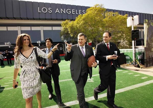 Tim Leiweke, center, president and chief executive of Anschutz Entertainment Group, walks with his daughter Francesca Leiweke after a news conference announcing that a naming rights deal had been reached with Farmers Insurance for the football stadium planned for downtown Los Angeles.