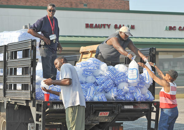 Carolyn Holley, at right, receives two free bags of ice from Baltimore Housing Authority employees after the June 29 derecho storm struck the region. Many were without power for as long as a week after the storm.