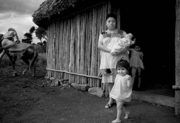 Jacinta Chi Tun, in doorway of her house, with her children. Monte Cristo, Yucatan, 1971.