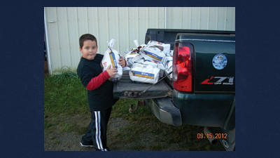 Hunter Ansell helps load potatoes on to the Boswell food pantry truck last Saturday as part of the Somerset County Potato Thrivent potato picking project.