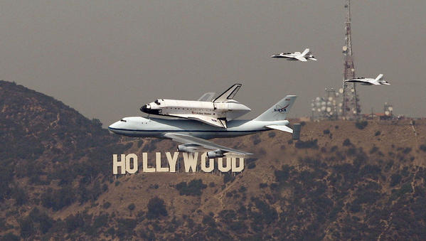 The space shuttle Endeavour passes the Hollywood sign.