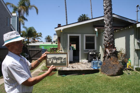 Leroy Jauman holds a photo of what his Huntington Beach home on Eighth Street looked like decades ago. His father planted two palm trees in front of the home to celebrate Leroy's birth.