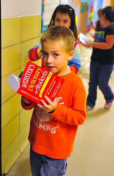 Emma K. Doub Elementary School third-grader Matthew Lintz peers from his newly-acquired dictionary Monday on his way to class. Several area Rotary clubs teamed together to provide dictionaries to third-grade students in Washington County schools.