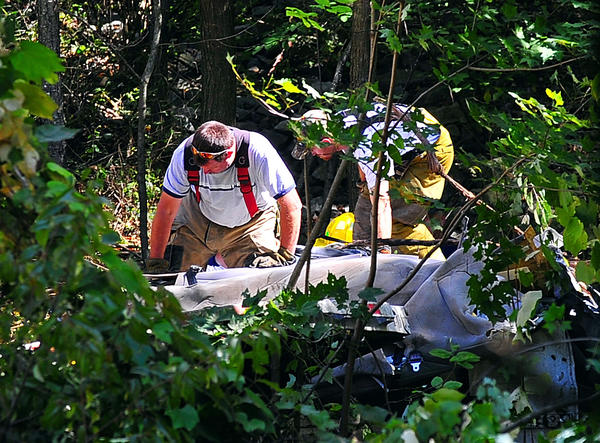 Rescue personnel work Monday on the cab of a tractor-trailer that skidded down a steep 400-foot embankment beside Interstate 68 west of Hancock.