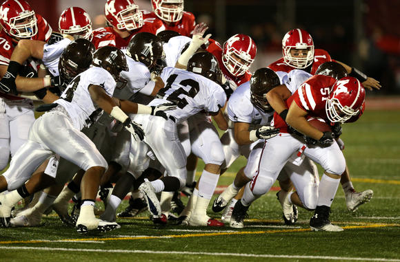 Marist's Steven McGugan (right) gains a first down against Joliet Catholic on Friday, September 21, 2012.