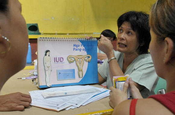 A health worker teaches women how to properly use a intra uterine device (IUD) during the World Population Day in Manila.