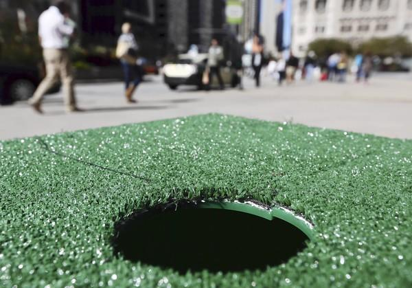 A hole is seen Monday where an oversize golf ball artwork was once positioned along North Michigan Avenue. The artwork, designed by Jeff Budzban, featured the Chicago skyline and was signed by actress Jenny McCarthy.