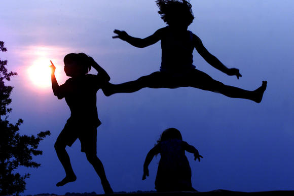 Childen jump on a trampoline while the sun sets