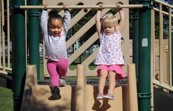 Gabriella Carey, 2 1/2, left, and Corbyn Smith, 2 3/4, both from Baltimore, make friends on the the playground at Federal Hill Park on a sunny, breezy day with temperatures in the high 60's to low 70's.