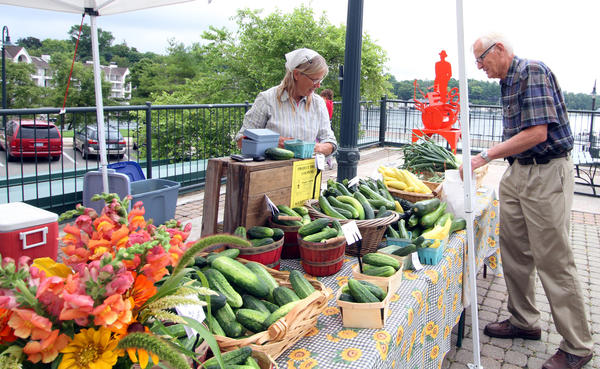 Rebecca Berg of Charlevoix, (left) packages up a selection of vegetables for a customer at a farmers market this summer, in downtown Charlevoix.