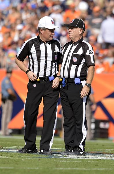 NFL referee Jerry Frump (37) and head linesman Charles Derrick talk during second quarter of the game between the Houston Texans against the Denver Broncos at Sports Authority Field.