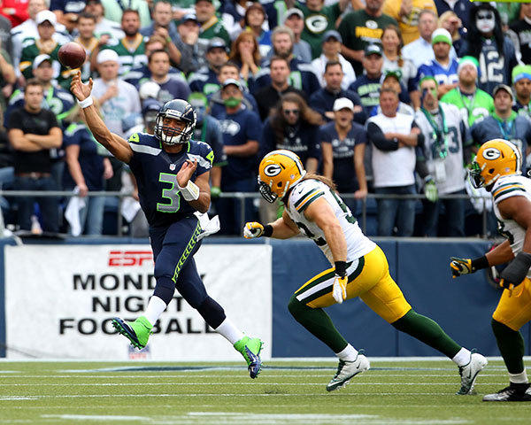 Russell Wilson #3 of the Seattle Seahawks throws downfield as Clay Matthews #52 of the Green Bay Packers pursues.