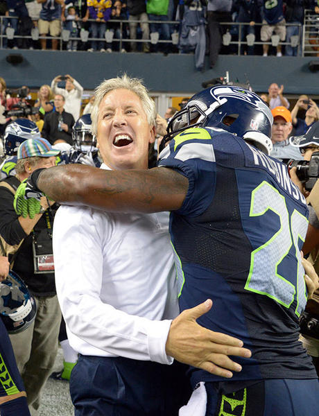 Seattle Seahawks coach Pete Carroll (left) and fullback Michael Robinson (26) celebrate at the end of the game against the Green Bay Packers at CenturyLink Field. The Seahawks defeated the Packers 14-12.