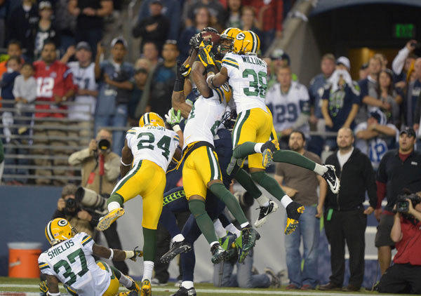 Seattle Seahawks receiver Golden Tate (81) catches a 24-yard touchdown pass as Green Bay Packers players Sam Shields (37), and Jarrett Bush (24), and Charles Woodson (21) and Jarrett Williams (38) defend on the final play.