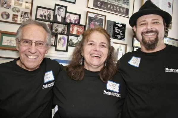 Celebrating 66 years in business as Pedrini Music are, from left, Manny Mora, wife Diane Pedrini Mora and son Joe Mora.